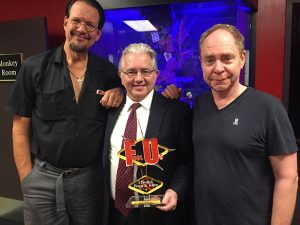 Paul Gertner holding the FU Trophy with Penn and Teller